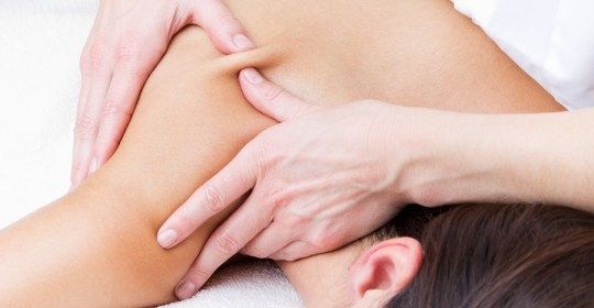 Woman enjoying shoulder massage at beauty spa